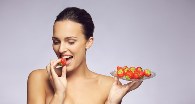 Gorgeous woman eating strawberry