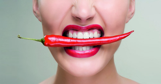 Woman with a red chili pepper between her teeth