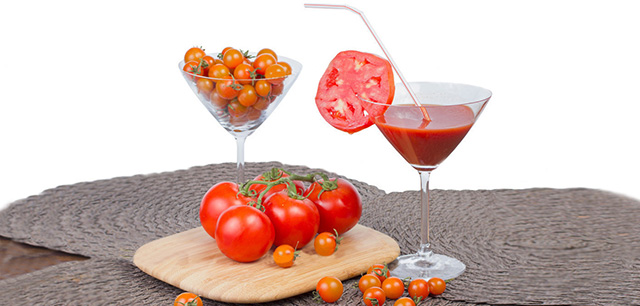 Tomato juice in the glass, orange cherry tomatoes and red tomato